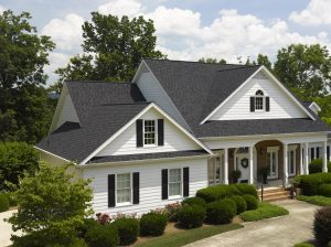 A beautiful two-story house with white siding and a gray asphalt shingle roof is surrounding by trees.