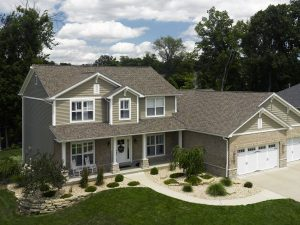An aerial image of a modern, two story home with an attached two-car garage. It features a brown asphalt shingle roof, beige siding, and white-frame windows.