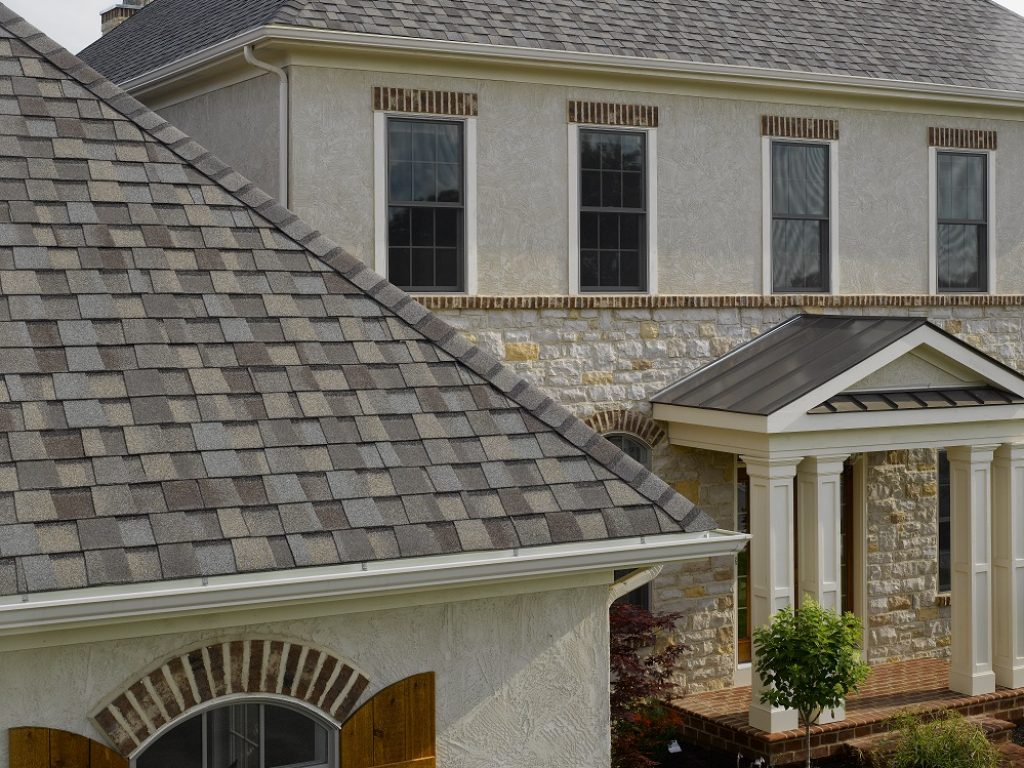 A close-up image of a GAF shingle roofing system on a modern home with stucco siding.